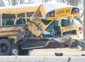 This photo, taken soon after the crash of a semi truck and an Archbold school bus, shows the damage to the left rear corner of the bus. Note: The flashing red light at the top right corner of the bus was still working after the crash. The bus, a 2014 model, has been declared a total loss.– photo by David Pugh