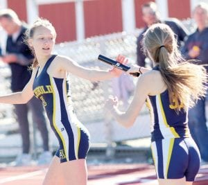 Montana Stamm, left, takes the handoff from Regan Ramirez in the 4x800, Tuesday, April 9. The Streaks won the race.– photo by Mary Huber