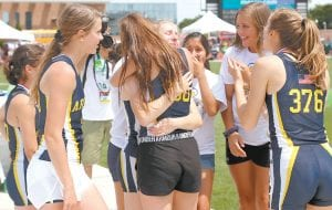 Gwynne Riley gets a hug from teammate Camryn Hudson, center, after Riley helped lead the AHS girls 4x400 relay to a state championship and the AHS girls track & field team was named Division III state runnersup for finishing second in total team points. Only five AHS girls competed in the state tournament in five events, but several other members of the team were there to show their support.– photo by Mary Huber