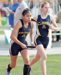 Left: Brittney Ramirez sprints away after taking the baton from Gwynne Riley in the 4x800-meter relay at the Div. III state track & field tournament, Friday, May 31. Archbold placed third in the event. Right: Kylie Sauder, left, and Riley run the final 75 meters in the 800-meter run. Sauder overtook several runners to finish fourth; Riley was seventh. There were 18 runners in the race.– photos by Mary Huber