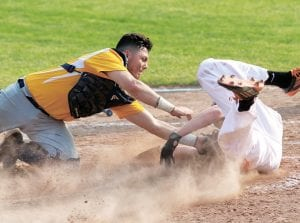 Blue Streak catcher Holden Galvan tags Coldwater's Will Broering out at home plate to prevent a run in the seventh inning of Archbold's regional final with the Cavaliers.– photo by Mary Huber