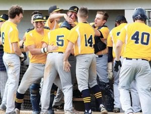 The Blue Streaks surround TJ Rice (5) after the senior scored in the fifth inning of Archbold's regional semifinal with Upper Sandusky. Kreighton Sims' hit to center field gave Rice the opportunity to score from second and give AHS a 2-0 lead.– photo by Mary Huber
