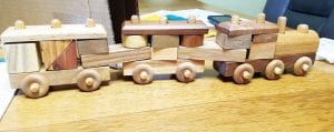 A puzzle train, one of almost 150 made by Lawrence Miller of Archbold. The train can be broken into pieces, which form a puzzle. Each piece is made from a different species of wood and is numbered, so the owner can look on a chart and learn the type. After almost 40 years, Miller has built his last train.– photo by Pam Graber