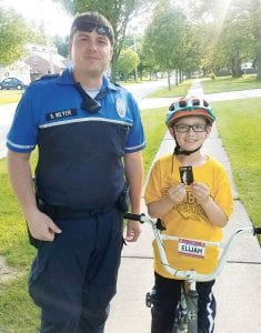 Brice Meyer, Archbold bicycle patrol officer, stands with Elijah Schmidt, Archbold, who just received a card to redeem for ice cream, all because he was wearing his bicycle helmet when Meyer spotted him. By handing out the cards, officers not only reward youngsters for wearing helmets, but also get to interact with them in a positive way.– photo by Pam Graber