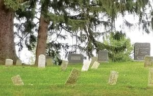 Headstones in the oldest part of the Johnson cemetery tilt at precarious angles. The German Township Trustees are discussing a plan to fix the problem.– photo by David Pugh