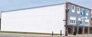 The south side of the Rupp Furniture building in the 200 block of North Defiance Street. Village council has discussed painting a mural on the blank white canvas since preparations began for the Sesquicentennial celebration in 2016, after the Red Cross Drug Store was torn down in 2015.– photo by David Pugh