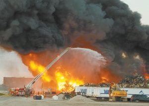 Fire rages through a large pile of scrap metal at the MetalX facility west of Delta just before 8 pm, Monday, Sept. 9. Fire departments from at least six northwest Ohio counties and two southeast Michigan counties worked together to fight the blaze, which is said to be contained on company property. As of Tuesday morning, the fire was still burning.– photo by David Pugh