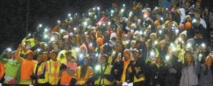 Members of the AHS student body shine the lights on their phones to signify the party's over for the Wauseon Indians. The Streaks shocked the Indians 38-0 to win the Lions Club trophy for the third straight year.– photo by Mario Gomez