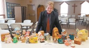 Bonnie Lauber, of St. Martin's Lutheran Church, Archbold, with roughly a quarter of the more than 100 piggy banks that were left to the church by the late Jerry Clevenger. Clevenger and his wife, Patricia, also deceased, collected the banks for years. They were used in a church fundraiser.– photo by Pam Graber