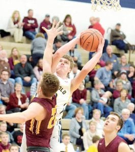 Archbold's DJ Newman takes a shot over the outstretched arm of Edgerton's Logan Showalter (22).– photo by Mario Gomez