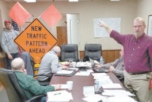 "Joe Short, president of the German Township Trustees, right, points out details of the new traffic signs the trustees plan to install on certain east-west roads that intersect with Co. Rd. 24 during the trustees' Monday, Dec. 9 meeting. Seated, are, clockwise from lower left: Kenneth ""Skip"" Leupp and Andy Brodbeck, trustees, and Keith Short, township fiscal officer. Standing with the sign is Jeff Aeschliman, township road maintenance worker.– photo by David Pugh"