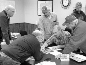 """Joe Short, seated, center, president of the German Township Trustees, discusses the location of a proposed new drainage tile, which will be constructed as part of a private project on Co. Rd. 25. Clockwise from top left: Andy Brodbeck, trustee; Josh King, township road superintendent; Jeff Aeschliman, township road maintenance worker; Roger Stuckey, a landowner on Co. Rd. 25; and Kenneth """"Skip"""" Leupp, trustee. Partially obscured is Keith Short, township fiscal officer.– photo by David Pugh"""