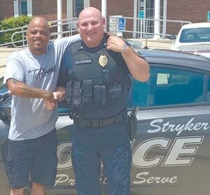 """Kenya Sayles, a truck driver who travels through Stryker, with Steve Schlosser, Stryker police chief. On Saturday, June 20, a Stryker officer stopped Sayles for allegedly failing to come to a complete stop at a stop sign, then drew his gun and pointed it at Sayles. Schlosser said the officer was """"not in the right mindset"""" when he pulled his weapon.– courtesy photo"""