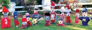 """A group of Christmas carolers adorns the lawn of Marlin and Shirley Beck, Pettisville. Each is made from a section of telephone pole and is """"dressed"""" with old shirts, hats and scarves. Inspiration for the group came from a trip to Michigan.– photo by D. J. Neuenschwander"""