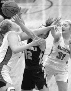 Karsyn Hostetler (12) is fouled by Wauseon's Kadence Carroll (31) as they go for a rebound. Wauseon's Hayley Meyer, left, also gets in on the action.– photo by Mary Huber