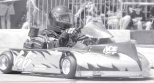 Logan Wyse, on the track in his racer powered by a flat head engine, is shown negotiating turns 1 and 2 on the oval track laid out downtown, Sunday, Aug. 8. Wyse swept the flat head class, winning two heats and the feature race.– photo by David Pugh