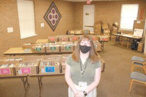 Sonya Huser, Archbold Community Library director, in the library community room, which was still set up for the Used Book Sale when this photo was taken. The board is considering expanding the current building by adding a second room of this size, specifically for children from infant to age 5.– photo by David Pugh