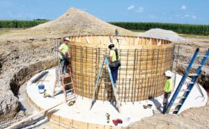 Construction workers were busy Friday, Aug. 20, building a wood structure that will become the form into which concrete is poured. It's part of the base for the new 200,000-gallon Archbold water tower. The project is expected to be completed next July.– photo by David Pugh